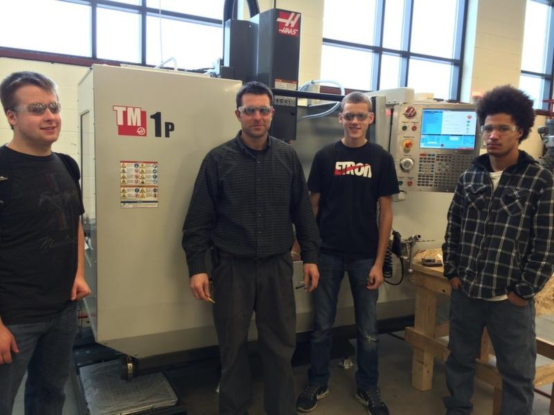 Teacher Matthew Komarowski and students demonstrate proper safety procedures with the new CNC machine.
