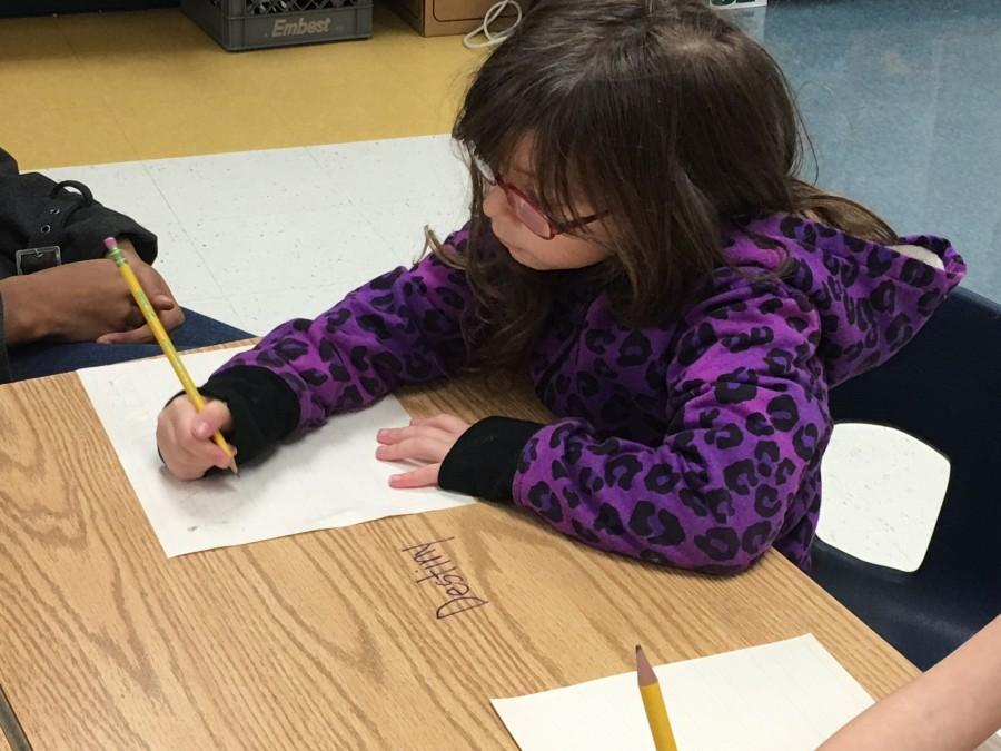 The children write their letters to Santa during class time.