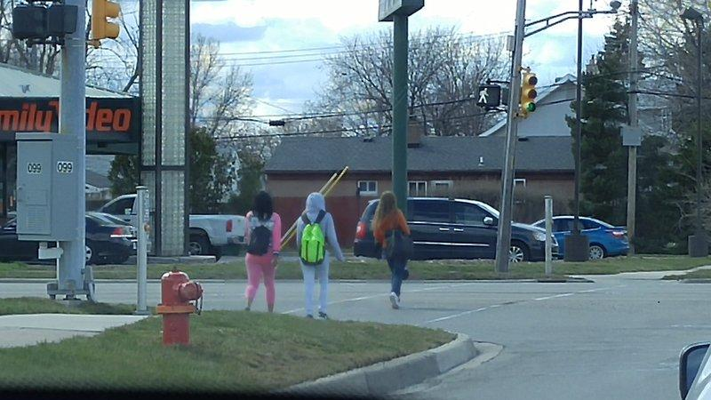 Students following traffic rules and using a crosswalk.