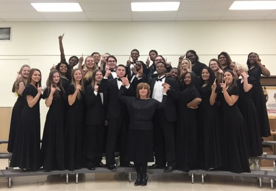 Symphonic choir proudly holding up a one for their achievement earning a one.