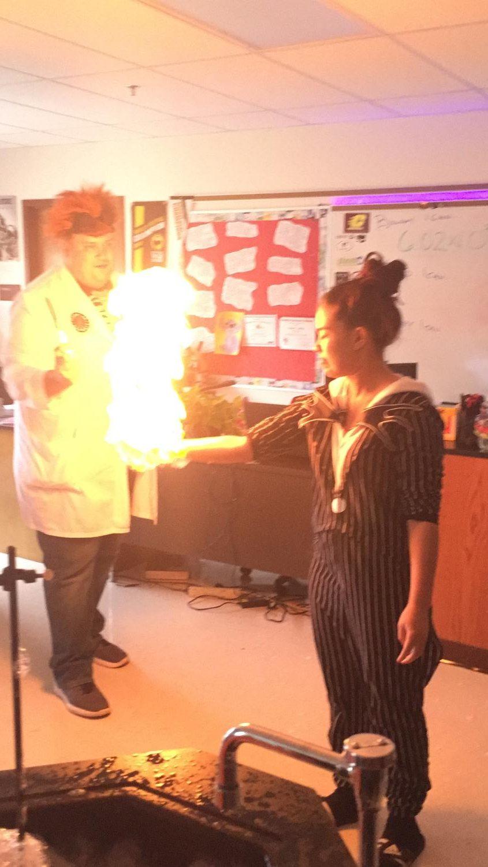 Science teacher, Smitka, letting a student make fire.