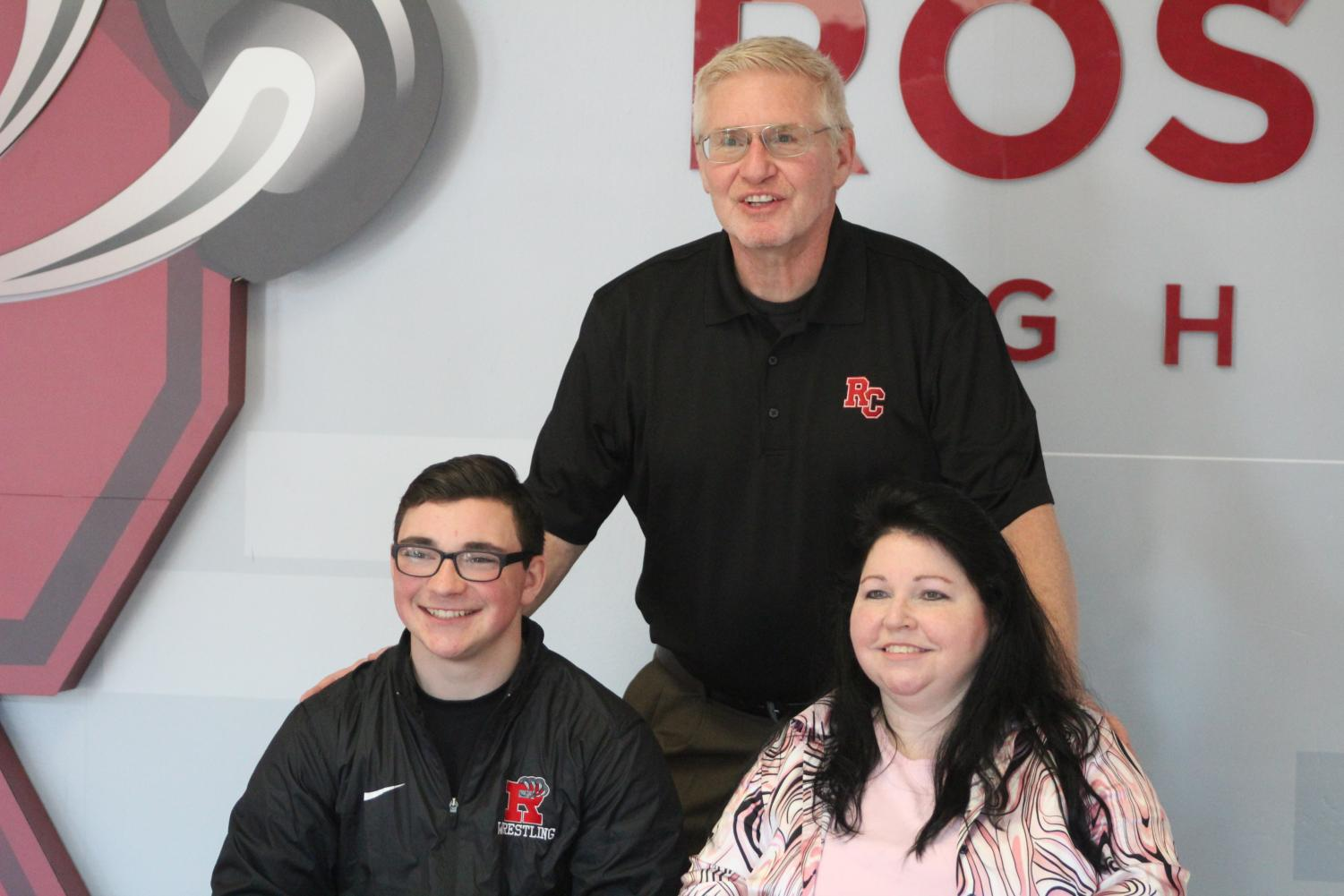 Mohn posing with his mom and new coach after signing with Rochester.