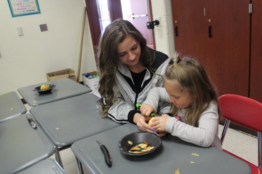 Senior Nina Croce helping a kindergartner use an apple slicer.