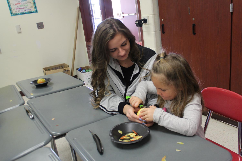 Senior Nina Croce helping a kindergartner use an apple slicer.