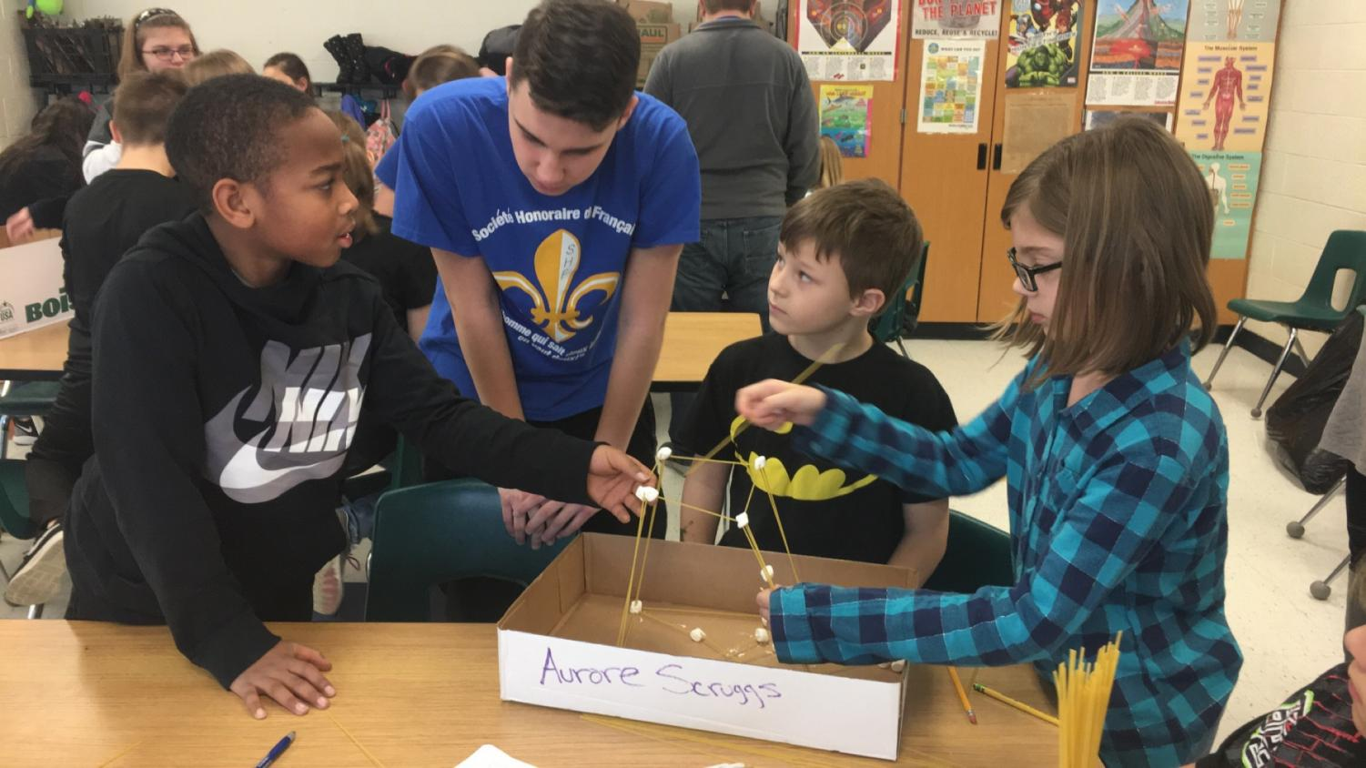 Junior Dawid Sikora helping Project Challenge kids strategize for their Eiffel Tower model.