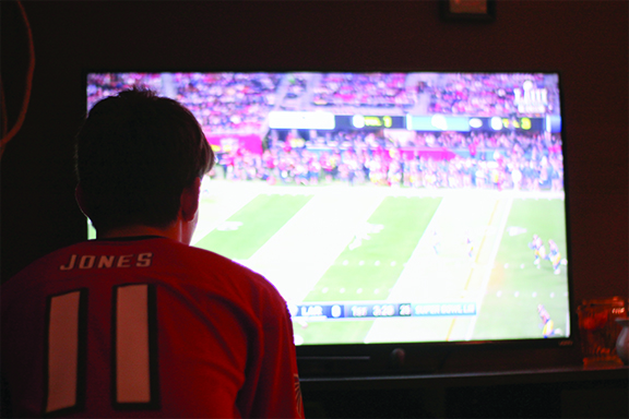 An avid football fan watching the Superbowl.