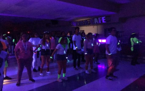 RHS students filling up the dance floor at Glowcoming with black lights and glow sticks shining all over.