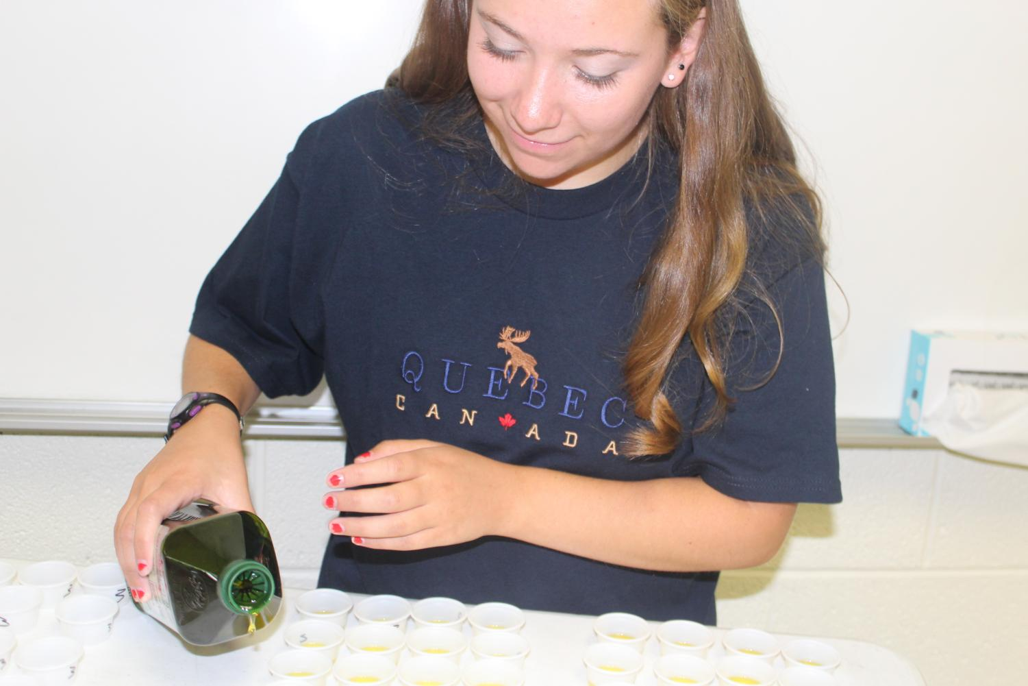 Senior Abigail Barnett helps guest speaker Aidan Pelish pour olive oil into tasting cups for the class to sample.