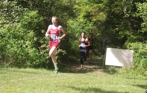 Junior Cameron Newman strides to keep up with Chippewa Valley in varsity race.