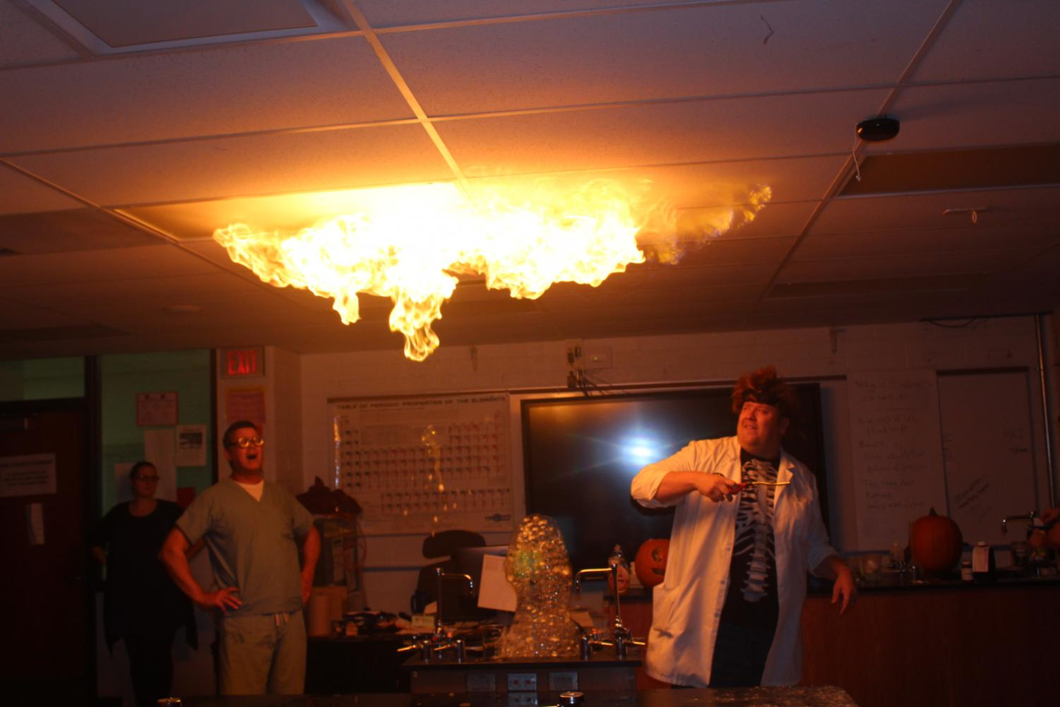 Biology teacher Bob Smitka lights bubbles in the air that cause a ripple effect across the ceiling.
