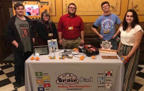 Current and former members of R.E.S.T. stand at their presentation table to showcase the video games they created.