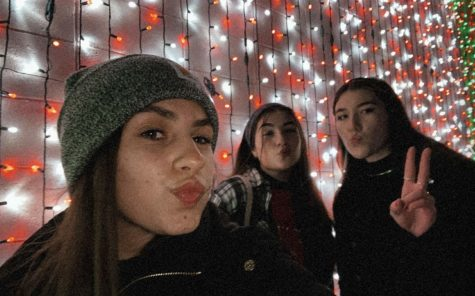 Seniors Dana DeLiso, Paige Lekki, and Olivia Morris out in front of an illuminated building in Downtown Rochester.